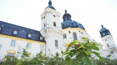 Close up white flower Ettal Abbey in background low angle Stock Footage