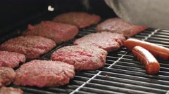 Man seasoning hamburgers and hot dogs on grill Stock Footage