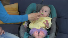 Baby with yellow bib eat vegetable pap sitting in car seat. 4K Stock Footage