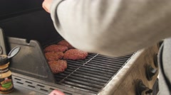 Man seasons hamburgers and hot dogs on grill Stock Footage