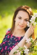 close up portrait of smiling young woman outside enjoying spring blossoms - stock photo