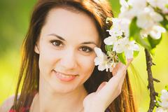 Close up portrait of smiling young woman outside enjoying spring blossoms Stock Photos