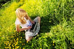 Young Caucasian woman using Laptop (Netbook) on nature, sitting in the grass  - stock photo