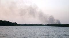 Fire burn with smoke beyond forest and pond Stock Footage