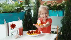 Stock Video Footage of Girl and a handful of cherry tomatoes. Child giving the viewer food. Smiling