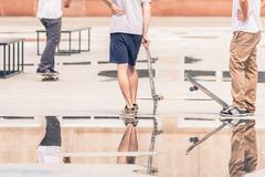 handsome guys with skateboard at freestyle park outdoors - stock photo