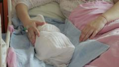 Infant sleeping in bed with mother who is caressing baby at maternity ward. Stock Footage