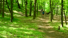 Young people walk in a lush green spring forest Stock Footage