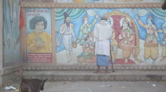 Dog and man pass the street while a man stands by a hindu wall painting. Stock Footage
