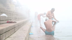 Stock Video Footage of Men scrubbing their bodies on shore of foggy Ganges river in Varanasi.