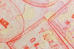 Different border stamps in a passport page - travel - stock photo