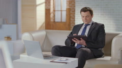 Businessman typing, scrolling pages on tablet, looking at camera Stock Footage