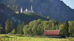 Morning sun on Bavarian Alps and on farm & Neuschwanstein Castle Germany Stock Footage