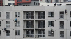 Workers climbers work on new build house wall Stock Footage