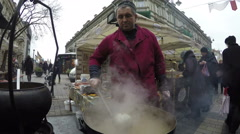 Chef cook pea soup in big pot boils at town square market.4K Stock Footage