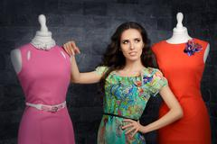 Elegant Woman in Fashion Store among Mannequins - stock photo