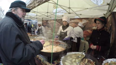 People buy fresh baked food from outdoor kitchen Stock Footage