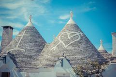 Close up of a conical roofs of a Trulli houses with painted symbols - stock photo