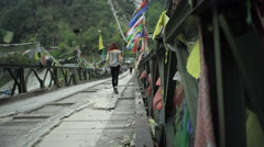 Girl walking over bridge with buddhist prayer flags, long shot Stock Footage