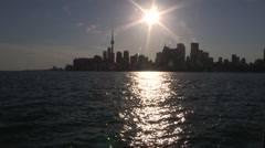Blazing sun reflecting off the water with Toronto skyline Stock Footage