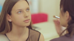Makeup artist applies concealer on the area under the eyes Stock Footage