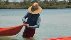 Man with hat in water and red kayak Stock Footage