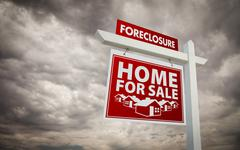 Red Foreclosure Home For Sale Real Estate Sign Over Ominous Cloudy Sky. Stock Photos