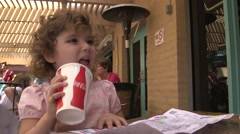 Cute little girl drinking coke at a restaurant Stock Footage