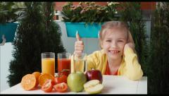 Child promoting a healthy juice. Smiling at camera and thumb up. Ok Stock Footage