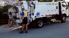 Garbage truck drives collecting garbage at Queens park Stock Footage