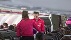 Air stewardess serving a passenger in the airplane Stock Footage