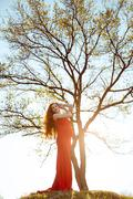 Young  pregnant woman relaxing and enjoying life in nature. Family tree - stock photo