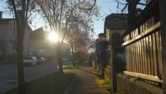 Walking along the pavement in suburbia at sunset - stock footage