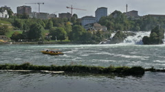 Yellow tourboat take tourists to Rhine Falls Switzerland city in background Stock Footage