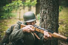 Stock Photo of Unidentified re-enactor dressed as German soldier aiming a rifle
