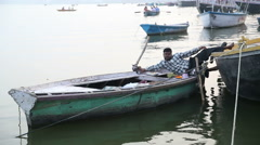 Man laying on a boat anchored in Varanasi preparing to paddle. Stock Footage