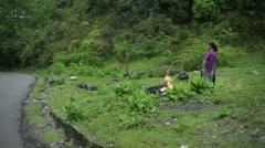 Woman burning trash in mountain village, long shot, shallow DOF Stock Footage