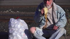 Homeless,eating banana at railyard Stock Footage