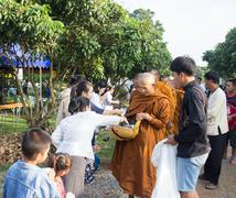 People put food offerings in a Buddhist monk's alms bowl for virtue Stock Photos