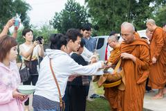 People put food offerings in a Buddhist monk's alms bowl to make great merit - stock photo