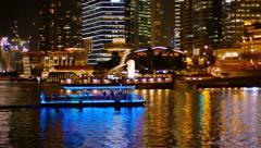 SINGAPORE - CIRCA JAN 2015: A tour boat, lit up in blue, cruises through Mari Stock Footage