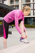 young woman tying her laces while out exercising - stock photo