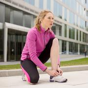 Young woman tying her laces while out running Stock Photos