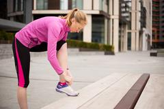 young woman tying her laces while out exercising. - stock photo