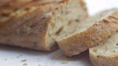 Loaf and slices of bread with grains on white background. Close up slow panorama Stock Footage
