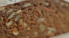 Loaf and slices of black bread with grains. Close up slow panorama Stock Footage