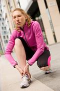 young woman touching an injured ankle - stock photo