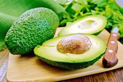 Avocado with napkin on board - stock photo