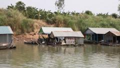 Sailing past a floating village on the Mekong river close pass-by woman in ho Stock Footage