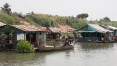 Sailing past a floating village on the Mekong river close pass-by with fishin Stock Footage